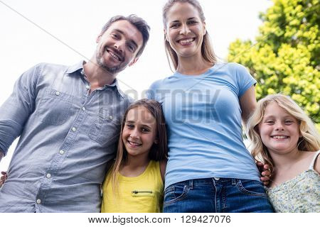 Happy family standing together with arm around in garden