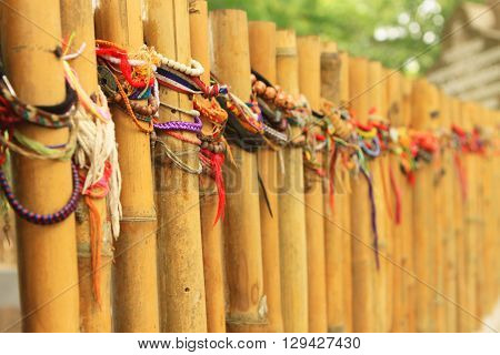 Bamboo fence wrapped in wrist bands left by travellers in Thailand