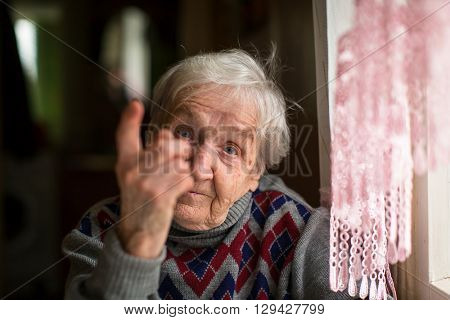 Elderly woman threatens with a finger looking at the camera.