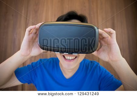 Smile happy man getting experience using VR-headset glasses of virtual reality at home much gesticulating hands asian male