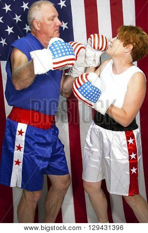 Man and woman sparring in patriotic boxing gear in front of an american flag .