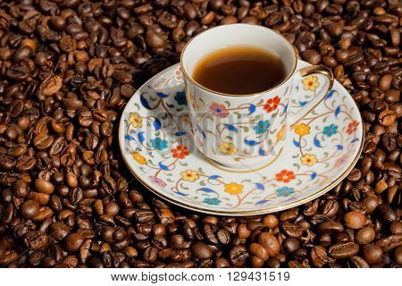 Turkish coffee in small cup with traditional patterns and background with coffee beans.