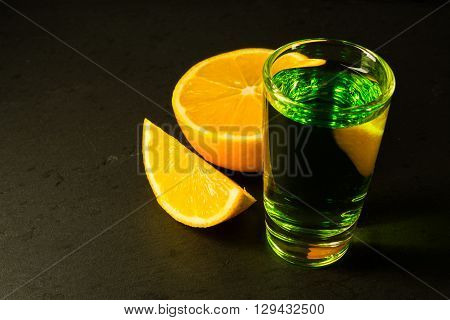 Absinthe on black background. Alcohol drink. Shot glass