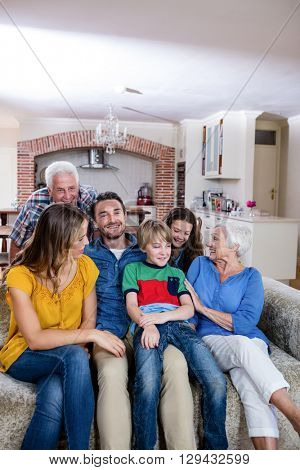 Multi-generation family sitting together on sofa at home