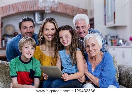 Portrait of multi-generation family sitting on sofa and using digital tablet at home