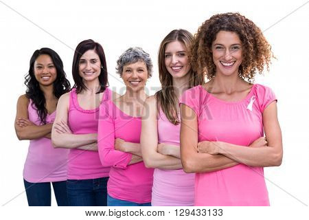 Smiling women in pink outfits standing in a line for breast cancer awareness on white background
