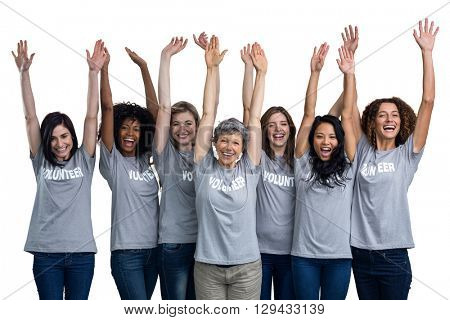 Portrait of happy volunteers standing with hands raised on white background