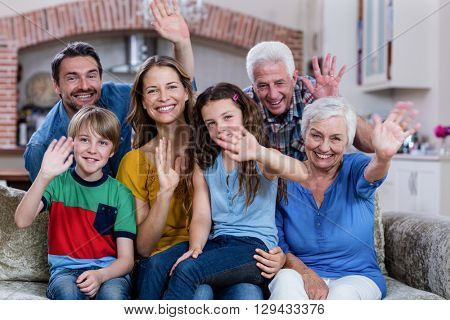 Portrait of multi-generation family sitting on sofa and waving hand at home