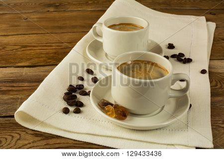Two cups of coffee on the white napkin copy space. Cup of coffee. Morning coffee. Coffee break. Strong coffee