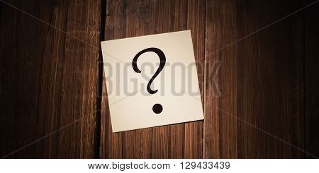 question mark against white paper fallen on wooden flooring