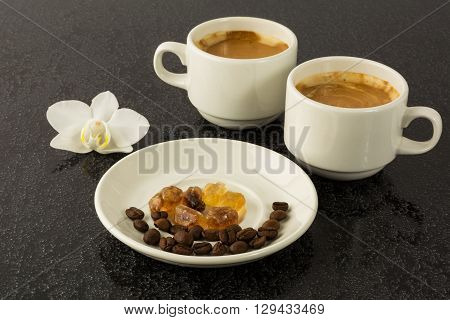 White coffee cups and white orchid on the black background. Cup of coffee. Coffee break. Morning coffee. Coffee cup