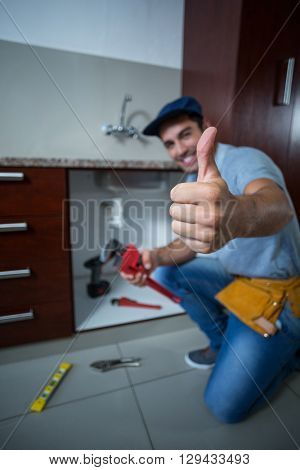 Portrait of happy man showing thumbs up while holding pipe wrench in kitchen