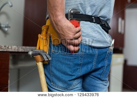Rear view of man putting pipe wrench in pocket while standing at home