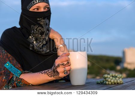 Woman Traditional Arabic Clothing At Outdoor Cafe Terrace Sitting at Wooden Table Morning Sunlight Blue Sky Background Focus on Hand with Tattoo Ornament