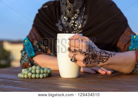 Close Up Image of Woman Traditional Muslim Clothing Touching Holding White Cup at Wooden Table Outdoor Morning Sunlight