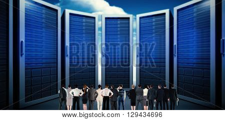 Rear view of multiethnic business people standing side by side against composite image of server room
