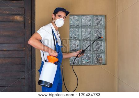 Portrait of worker spraying chemical on window