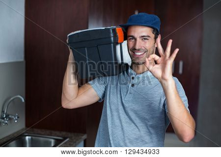 Portrait of smiling man carrying toolbox while showing ok sign in kitchen