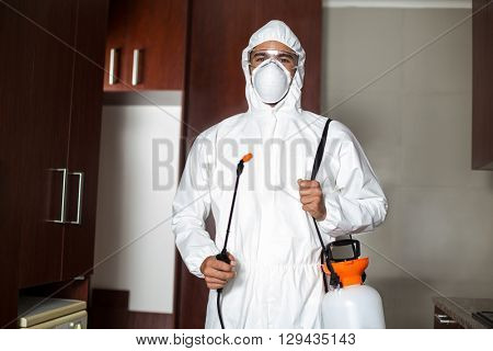 Portrait of pest worker in protective suit standing at home