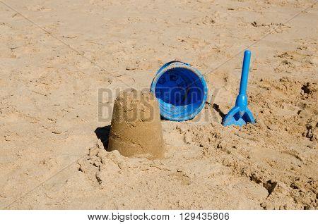 Sandcastle bucket and spade on beach in the sun