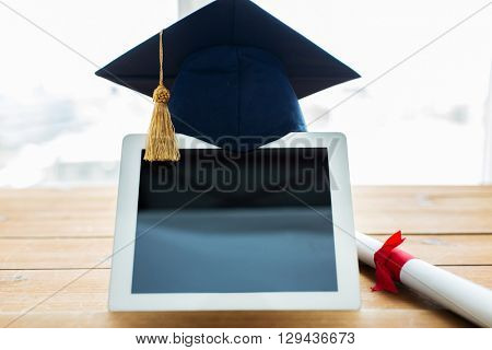 education, graduation, technology and e-learning concept - close up of tablet pc computer with mortarboard and diploma scroll on wooden table