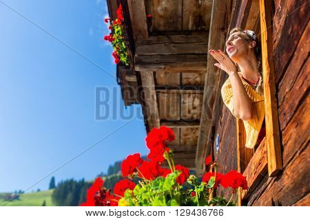 Woman at window of mountain hut in alps blowing a kiss to lover