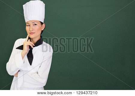 Portrait of thoughtful female cook in kitchen against image of a chalkboard