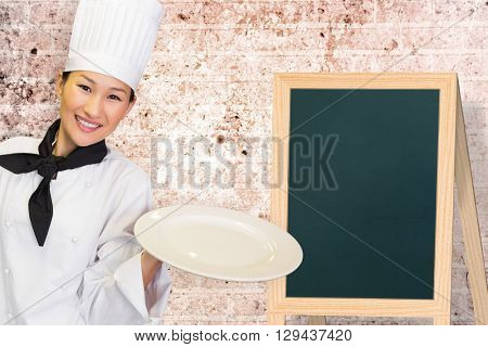 Smiling female cook holding empty plate in kitchen against image of a wall