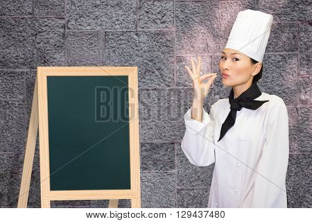 Smiling female cook in the kitchen against image of a wall