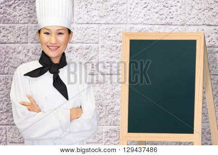 Portrait of smiling female cook in kitchen against image of a wall