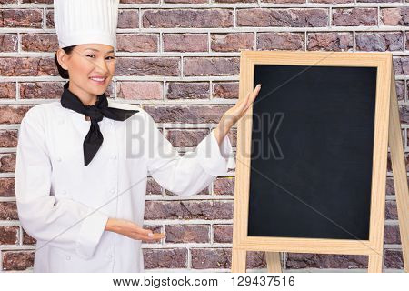 Portrait of a smiling female cook in kitchen against image of a wall
