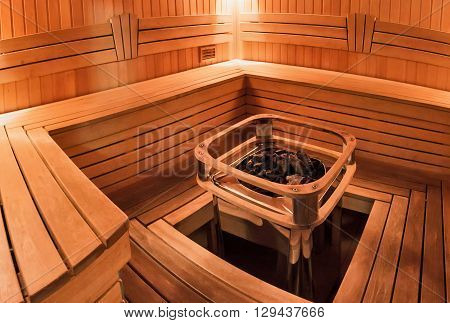 Light wooden sauna with bench and hot stones