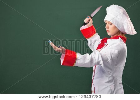 Pretty chef slicing with knife against image of a chalkboard