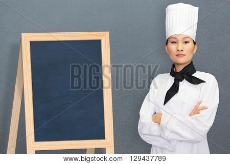Portrait of confident female cook in kitchen against grey