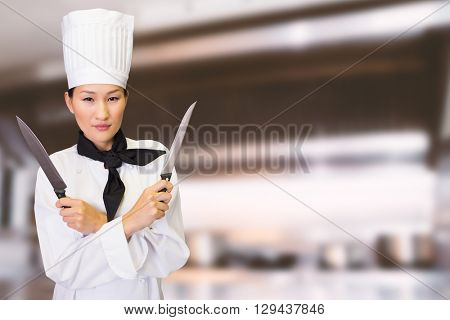 Confident female cook holding knives in kitchen against chrome counter with copy space