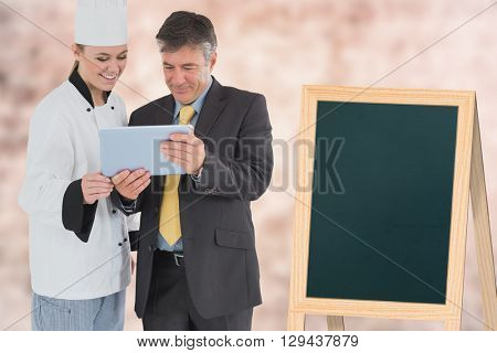 A cook showing a tablet to a businessman against image of a wall