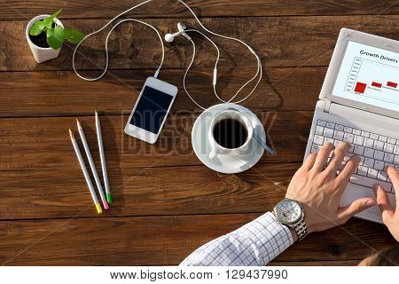 Man working on computer presentation sitting at unusual handcrafted rough wooden desk overhead top view coffee mug with many office supplies in creative disorder
