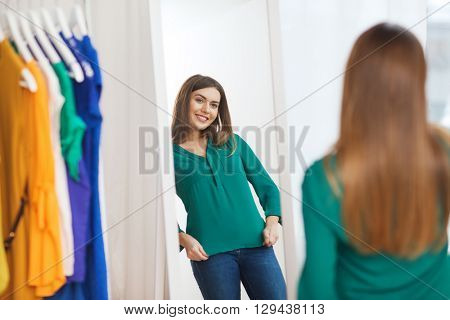 clothing, fashion, style and people concept - happy woman choosing clothes and posing at mirror at home wardrobe