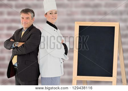A cook posing with a businessman against image of a wall