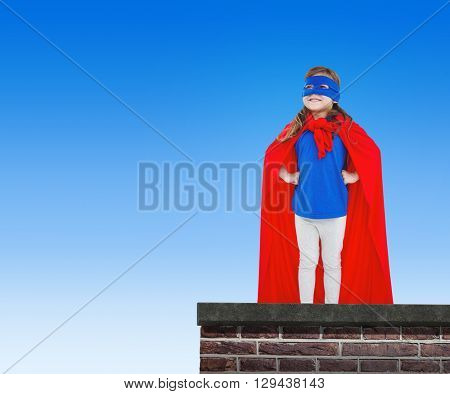 Masked girl pretending to be superhero against red brick wall