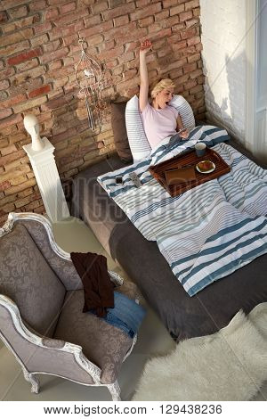 Young woman stretching in bed in the morning, yawning.