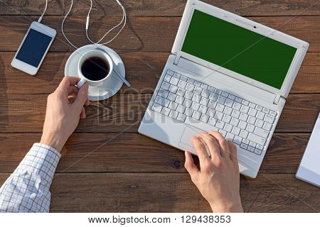 Man working on Computer at wooden Desk overhead View Business Chart on Laptop Screen Office on Table Telephone Coffee Mug green Laptop Screen