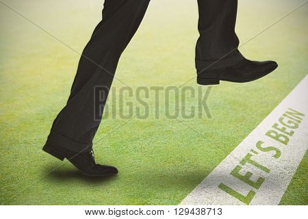 Businessman stepping against grassy landscape