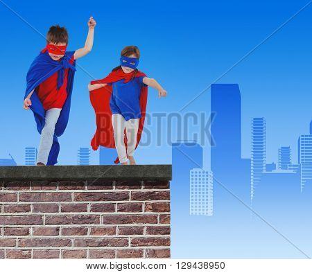 Masked kids walking pretending to be superheroes against red brick wall