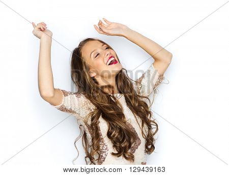 people, style, holidays and fashion concept - happy young woman or teen girl in fancy dress with sequins and long wavy hair dancing at party