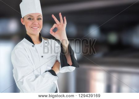 Happy female chef gesturing ok sign against large vats of beer