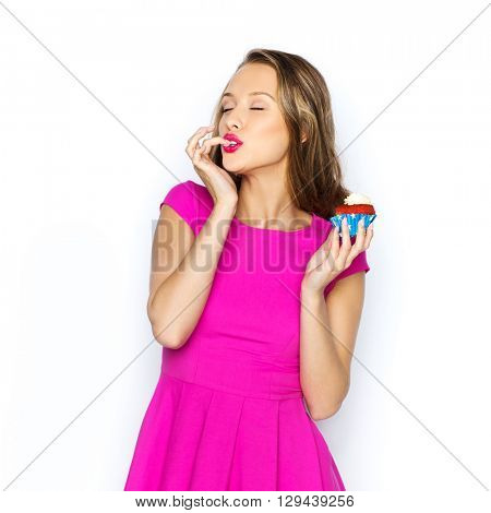 people, holidays, party, junk food and celebration concept - happy young woman in pink dress eating birthday cupcake
