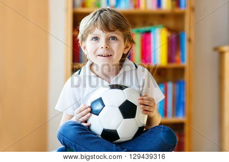 Excited little preschool kid boy with ball watching soccer european cup game on tv. Funny child fan having fun and cheering winning football team. Champions league concept.