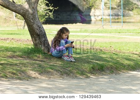 Cute little girl sitting on the grass in a park with a mobile phone in her hands and stares at the phone's screen