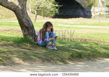 Cute little long-haired girl sitting on the grass in a park with a mobile phone in her hands and stares at the phone's screen